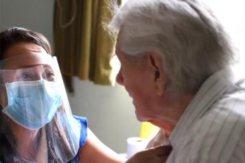 Care home worker in PPE and resident