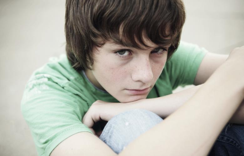 Young boy sitting down hugging his knees